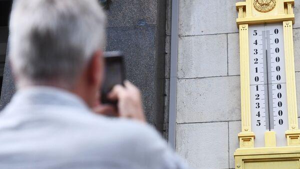Mężczyzna fotografuje termometr na budynku Dumy Państwowej w Moskwie - Sputnik Polska