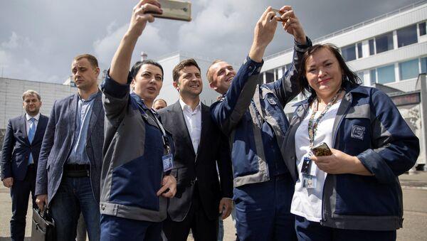 Prezydent Ukrainy Wołodymyr Zełenski robi sobie zdjęcie z pracownikami Czarnobylskiej Elektrowni Atomowej w czasie uroczystości oddania do użytku nowego sarkofagu nad czwartym uszkodzonym reaktorem jądrowym w Czarnobylu - Sputnik Polska