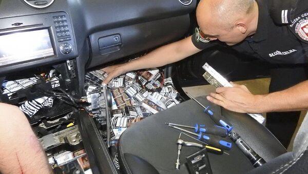 Polski celnik wyciąga papierosy ukryte w samochodzie mieszkańca Kaliningradu - Sputnik Polska