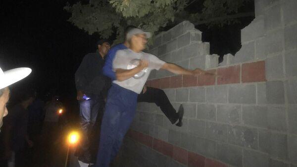 Ludzie przeskakują mur w miejscu zatrzymania byłego prezydenta Kirgistanu Ałmazbeka Atambajewa - Sputnik Polska