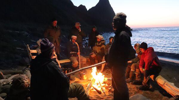 Członkowie wyprawy wokół ogniska na brzegu zatoki Szczukina na wyspie Urup (wyspa południowej grupy Wielkiego Grzbietu Wysp Kurylskich) - Sputnik Polska