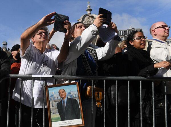 Ludzie zgromadzeni przed kościołem przed ceremonią pogrzebową dla byłego prezydenta Francji Jacquesa Chiraca - Sputnik Polska