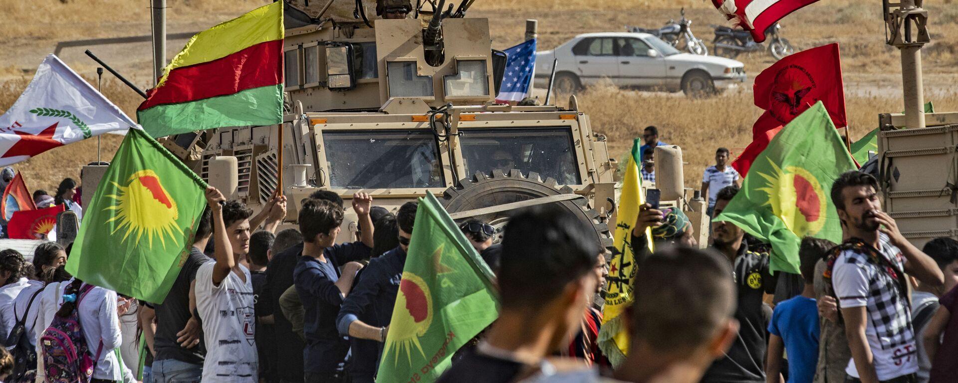 Syryjscy Kurdowie wokół amerykańskich pojazdów opancerzonych podczas demonstracji przeciwko tureckim zagrożeniom w pobliżu bazy wojskowej w syryjskiej prowincji Hasake - Sputnik Polska, 1920, 23.10.2019