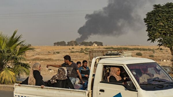 Arabscy i kurdyjscy cywile uciekają po bombardowaniu syryjskiego miasta Ras Al-Ajn przez Turcję - Sputnik Polska