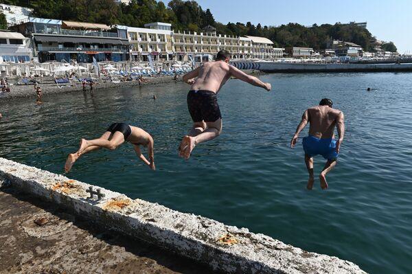"""Mężczyźni skaczą z molo na plaży """"Primorskij"""" w centralnej części miasta Soczi - Sputnik Polska"""