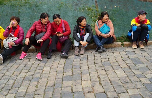 Zagraniczni turyści na krawężniku w pobliżu Placu Czerwonego w Moskwie  - Sputnik Polska
