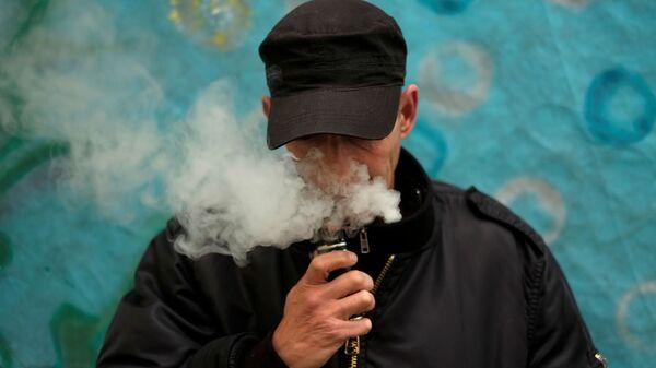 Mężczyzna pali elektronicznego papierosa - Sputnik Polska