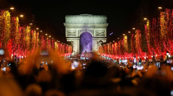 Widzowie podczas świątecznego pokazu świetlnego pod Łukiem Triumfalnym w Paryżu - Sputnik Polska