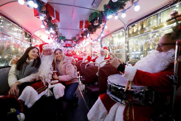 Muzykanci w kostiumach Mikołajów w autobusie, Petersburg  - Sputnik Polska