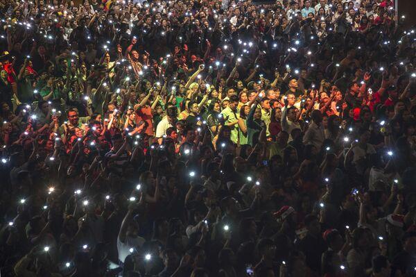 Chrześcijanie z zapalonymi latarkami na telefonach podczas mszy w Indonezji  - Sputnik Polska