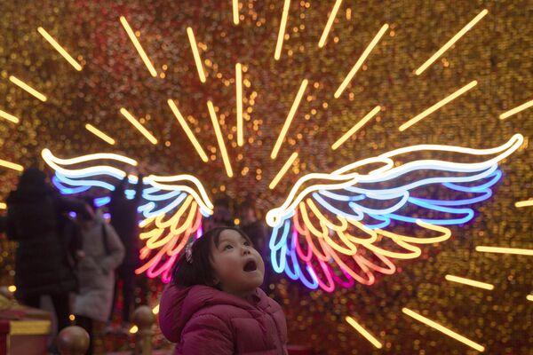 Dziewczynka spaceruje w świątecznie oświetlonym parku w Pekinie  - Sputnik Polska