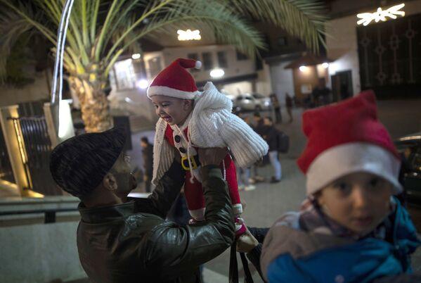 Mężczyzna bawi się z dzieckiem przed rozpoczęciem mszy w Gazie  - Sputnik Polska
