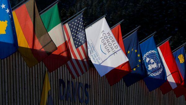 Flagi narodowe kilku państw i logotyp Światowego Forum Ekonomicznego w Davos - Sputnik Polska