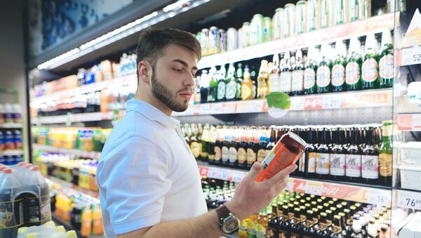 Młody mężczyzna wybiera piwo w sklepie - Sputnik Polska