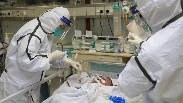 Pracownicy służby zdrowia w kombinezonach ochronnych nad pacjentem z wykrytym koronawirusem - Sputnik Polska
