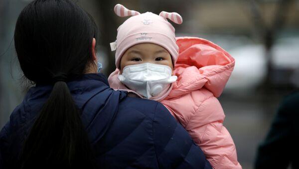 Kobieta z dzieckiem w maskach medycznych na jednej ulic w Pekinie - Sputnik Polska