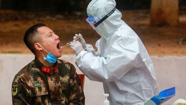 Sanitariusz pobiera próbkę od policjanta w celu wykonania testu na koronawirusa po jego powrocie z wakacji w Chinach - Sputnik Polska