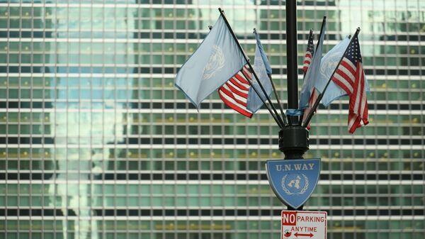 Flagi USA i ONZ pod budynkiem kwatery głównej ONZ w Nowym Jorku - Sputnik Polska