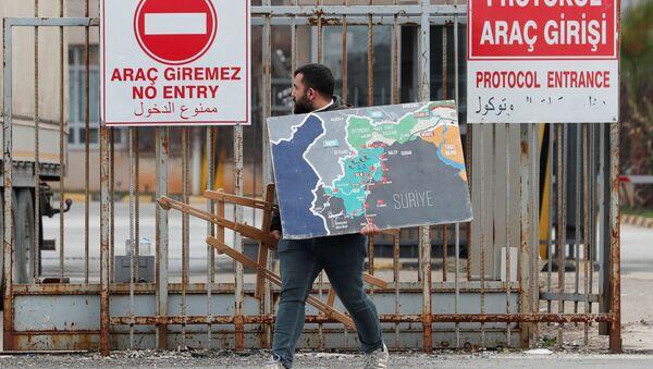 Syryjczyk wjeżdża do Turcji przez bramę graniczną Chilvegozu, położoną naprzeciwko syryjskiego komercyjnego punktu kontrolnego Bab al-Hawa - Sputnik Polska