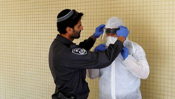 Izraelski policjant pomaga inspektorowi Ministerstwa Zdrowia nałożyć sprzęt ochronny przed mieszkaniem osoby poddanej kwarantannie - Sputnik Polska