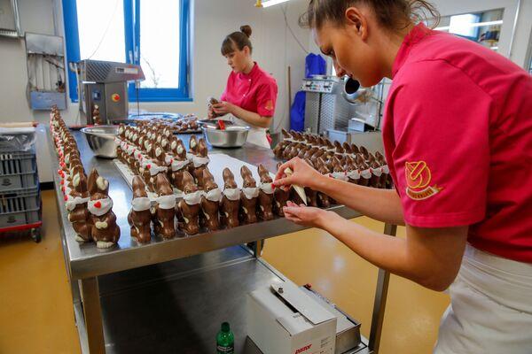 Pracownicy przygotowują czekoladowe króliki wielkanocne w maskach ochronnych w piekarni Baeckerei Bohnenblust w Bernie w Szwajcarii - Sputnik Polska