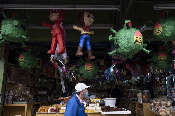 Mężczyzna w masce ochronnej przechodzi obok cukierni z zabawkami w kształcie koronawirusa, Meksyk - Sputnik Polska