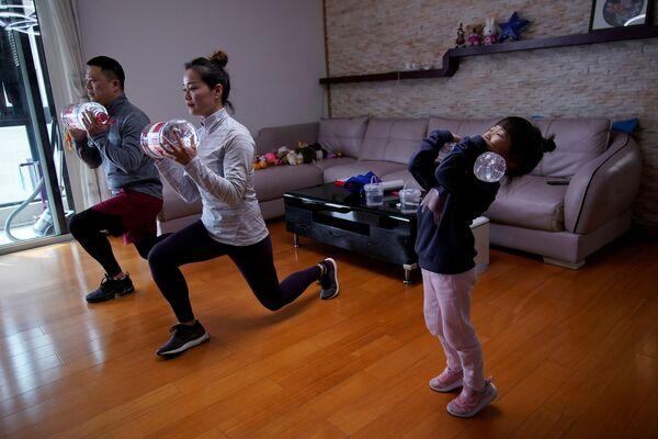 Chińska rodzina ćwiczy w domu, używając butelek z wodą - Sputnik Polska