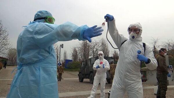 Rosyjscy eksperci wojskowi dezynfekują kombinezony po wizycie w szpitalu dla osób starszych w Bergamo, we Włoszech, w celu walki z zakażeniem koronawirusem COVID-19 - Sputnik Polska