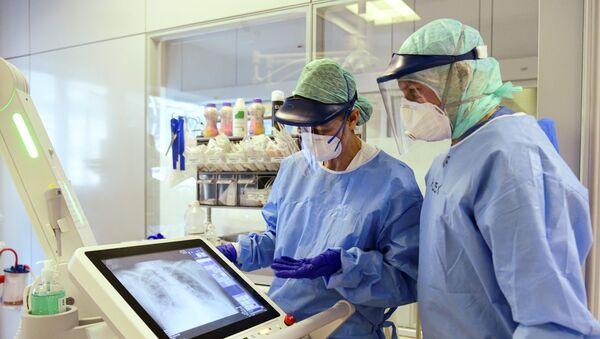 Pracownicy kliniki w Bergamo w maseczkach ochronnych analizują zdjęcie rentgenowskie płuc pacjenta chorego na koronawirusa - Sputnik Polska