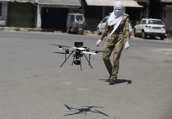 Indyjski policjant obserwuje drona, który sprawdza przestrzeganie kwarantanny - Sputnik Polska