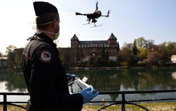 Włoski carabinieri obsługuje drona w celu sprawdzenia, czy ludność wdraża środki wprowadzone przez rząd w związku z koronawirusem w Turynie we Włoszech - Sputnik Polska