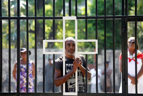 Ludzie przy zamkniętej bramie kościoła podczas świąt wielkanocych na Haiti - Sputnik Polska