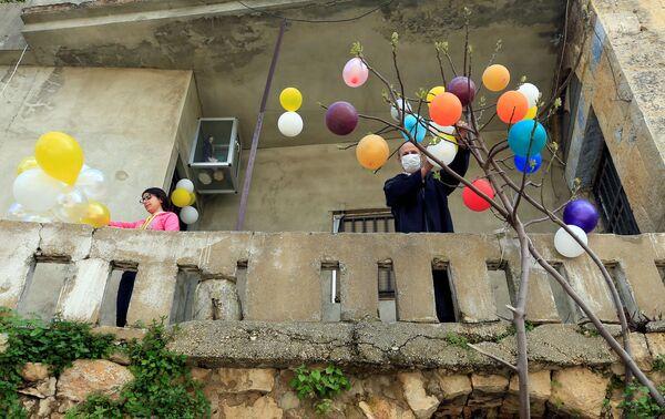 Mężczyzna ozdabia drzewo balonami podczas Wielkanocy w Libanie - Sputnik Polska