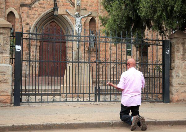 Mężczyzna modli się przed zamkniętym kościołem w Zimbabwe - Sputnik Polska
