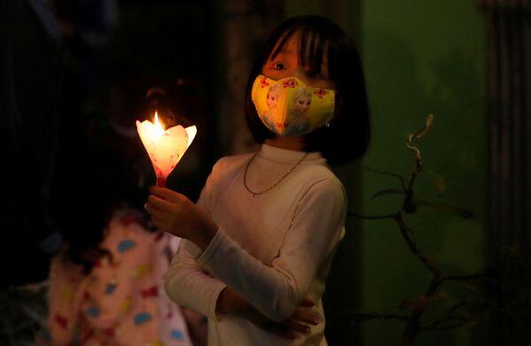 Dziewczynka w masce ochronnej podczas świąt wielkanocnych w Wietnamie - Sputnik Polska