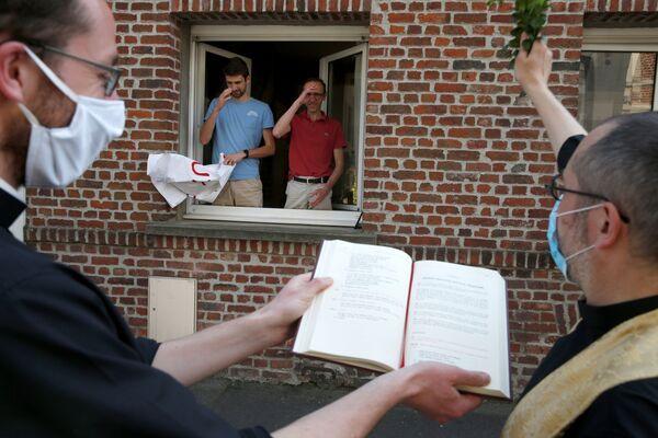 Francuski ksiądz błogosławi ludzi w niedzielę wielkanocną w Arras - Sputnik Polska