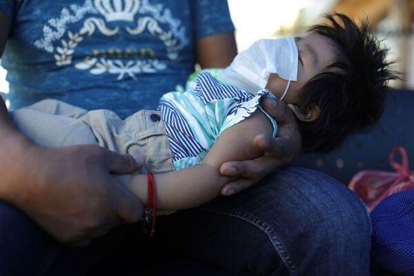 Dziecko śpi w masce na rękach ojca - Sputnik Polska