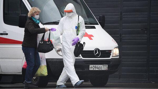Lekarz pogotowia w kombinezonie ochronnym pomaga pacjentce przenieść rzeczy do centrum kwarantanny w Kommunarce - Sputnik Polska