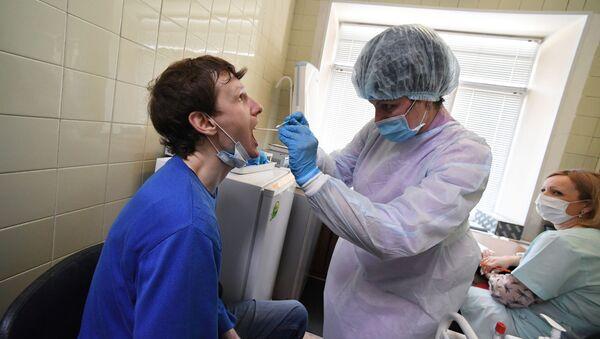 Epidemiolog pobiera wymaz z błony śluzowej jamy ustnej pacjenta w celu wykonania testu na koronawirusa we Władywostoku - Sputnik Polska