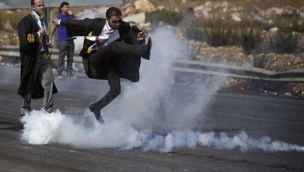 Palestyński adwokat kopie balon z gazem łzawiącym podczas akcji protestacyjnej w mieście Ramallach - Sputnik Polska