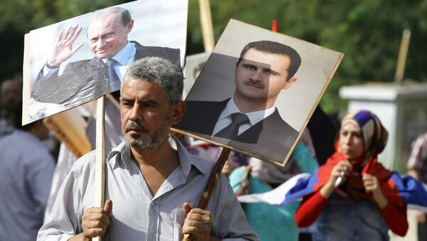 Syryjczyk niesie portrety al-Asada i Putina - Sputnik Polska