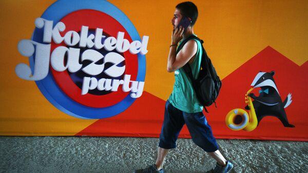 Młody człowiek na tle plakatu corocznego międzynarodowego festiwalu jazzowego Koktebel Jazz Party w Koktebelu - Sputnik Polska
