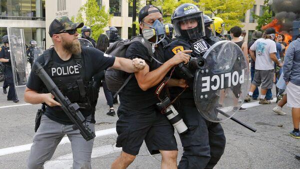 Policjanci popychają dziennikarza podczas protestów w USA - Sputnik Polska
