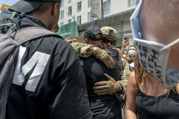 Protestujący i funkcjonariusze Gwardii Narodowej USA obejmują się podczas demonstracji po śmierci George'a Floyda w Los Angeles - Sputnik Polska