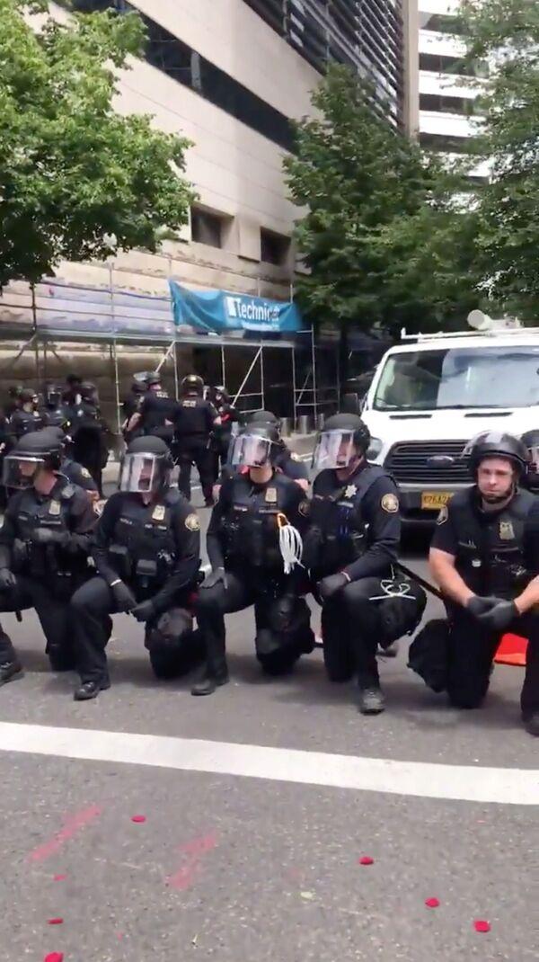 Funkcjonariusze policji klęczący w solidarności z protestującymi w Portland, USA - Sputnik Polska