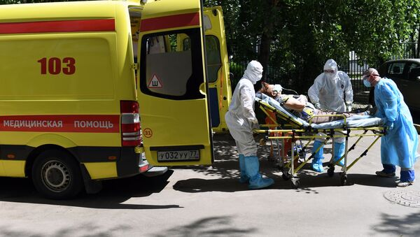 Sanitariusze i kierowca przenoszą pacjenta z podejrzeniem koronawirusa do karetki pogotowia - Sputnik Polska
