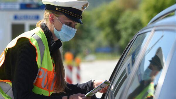 Niemiecki policjant w masce ochronnej podczas sprawdzania samochodu na przejściu granicznym między Austrią a Niemcami - Sputnik Polska