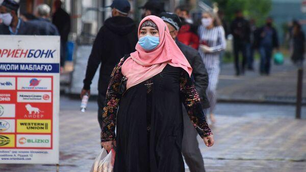 Kobieta w masce ochronnej na jednej z ulic Duszanbe - Sputnik Polska