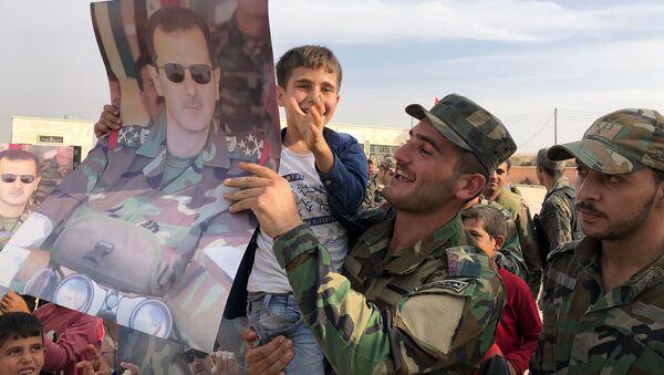 Dzieci i wojskowi z plakatami z portretem prezydenta Syrii Baszara al-Asada w mieście Manbidż w Syrii wyzwolonym przez syryjską armię rządową - Sputnik Polska