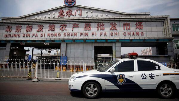 Radiowóz policyjny przy zamkniętym rynku Sinfadi w Pekinie - Sputnik Polska